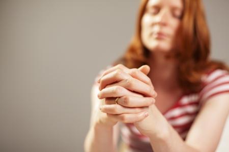 manos orando: Imagen de detalle de una mujer joven rezando DOF muy bajo, foco en las manos Foto de archivo