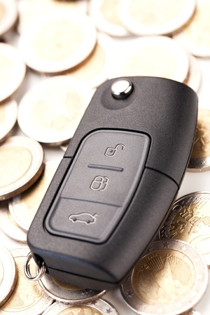 key fob: A modern cars remote control starter key laying over a pile of coins - a concept about car costs or expenses. Stock Photo