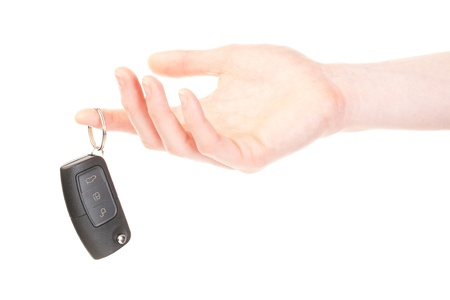 A female hand holding a modern cars remote control key. Isolated on white background.
