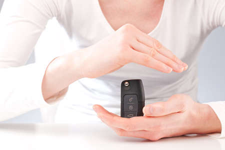 key fob: Female hands holding a modern cars remote control key and protecting it.