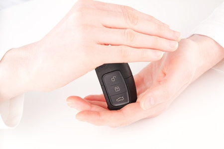 key fob: A female hand holding a modern cars remote control key between her hands and protecting it. Stock Photo