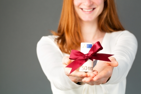 A happy woman presenting or giving Euro bills as a gift or a present.