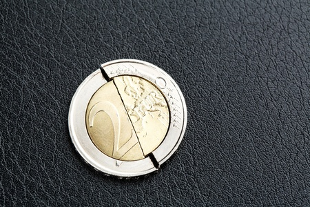 A macro image of a broken two Euro coin on black leather background. photo