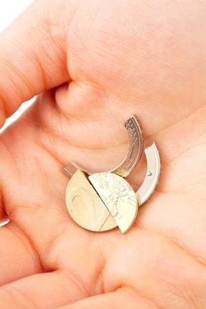 Een conceptueel beeld over de financiën of geld - een munt van 2 euro Broek in stukken in een vrouwelijke hand.