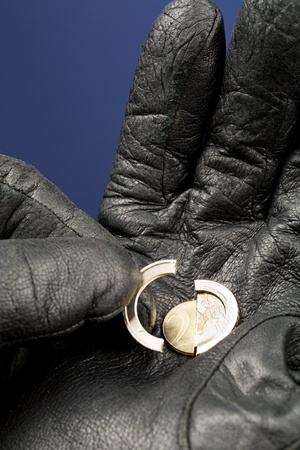 A broken coin of 2 Euro in a hand with leather glove. photo