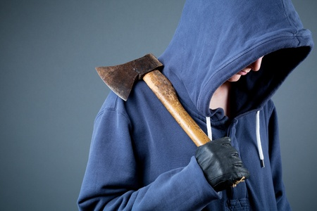 hooded top: A dangerous female with a hooded sweater holding an axe. Stock Photo