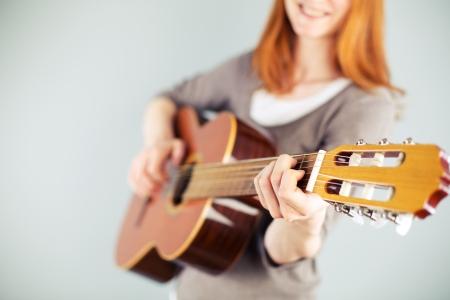 Een jonge blanke vrouw spelen van een klassieke gitaar en glimlachend.