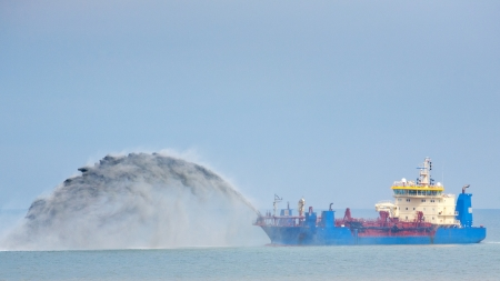 A blue dredging ship working in the North Sea. Stock Photo