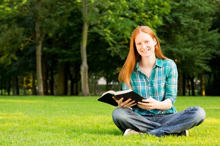 christian women: A Christian woman holding a Bible and smiling at the camera, photographed in a public park. Stock Photo
