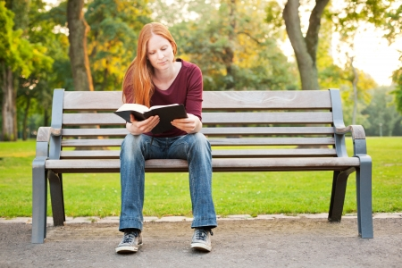 A casual young woman sitting on a bench in a park and reading her Bible. photo