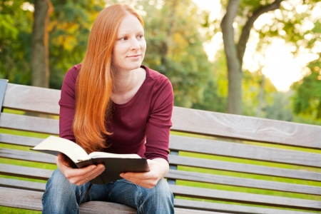 A female believer meditating on the Bible in a public park.