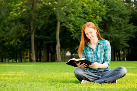 A Caucasian young Christian woman reading a Bible outdoors in a public park.
