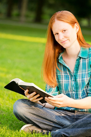 A Christian woman holding a Bible while sitting in a park and smiling at the camera.