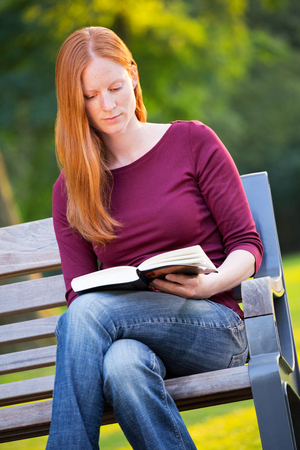 A young woman with red hair reading a book on a bench in a park. photo