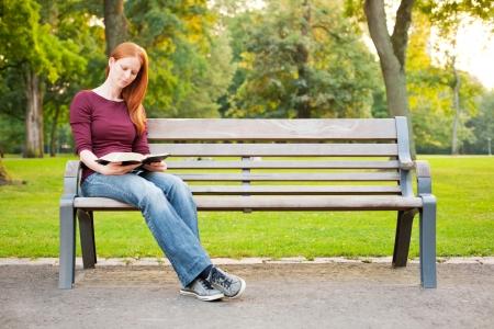 Egy fiatal nő ül egy padon a parkban, és tanulmányozza a Bibliát.