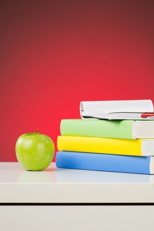 A green apple and textbooks on a white desk with a red background  photo