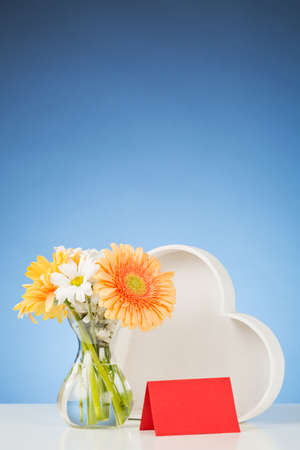 A Bouquet Of Flowers In A Vase Next To A White Wooden Heart With