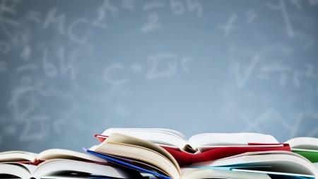образование: Многие открытые книги лежа перед синем фоне с различными формулами и буквами.