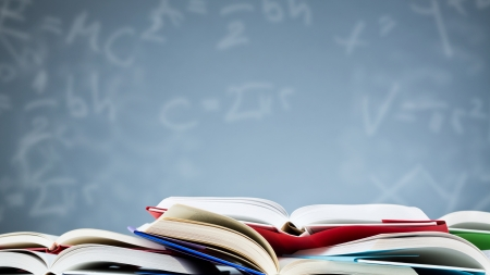 physics background: Many open books lying flat before a blue background with various formulas and letters.