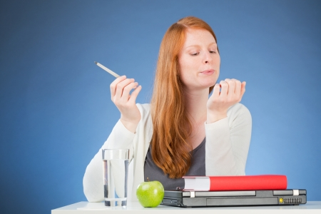 depict: A bad female student working on her nails instead of studying, could depict boredom or lack of interest.