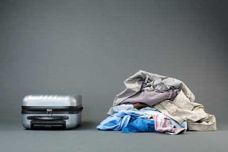 messy clothes: Trip preparation - a messy pile of clothes next to  a lightweight suitcase. Stock Photo