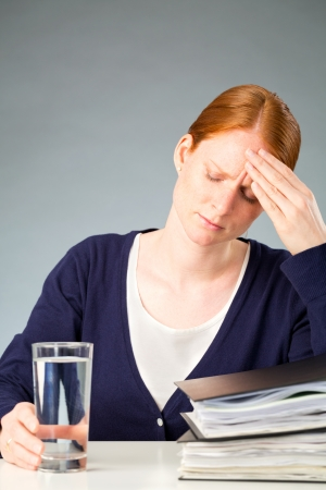 A young businesswoman with a glass of water experiencing a headache caused by stress at work. photo