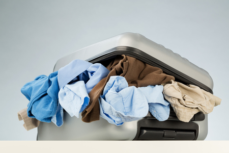messy clothes: A suitcase over-packed with too much and messy clothes lying on a white surface.