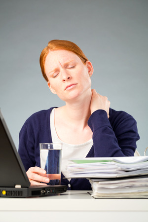 A young woman suffering from neck pain at work, sitting behind a desk with a computer and documents. photo