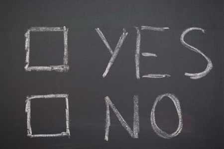 disapprove: The words Yes and No next to square check boxes drawn with chalk over a blackboard. Stock Photo