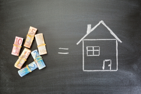 sign equals: Rolled up Euro bills next to a hand drawn house on a blackboard with an equals sign between them, top view. Stock Photo