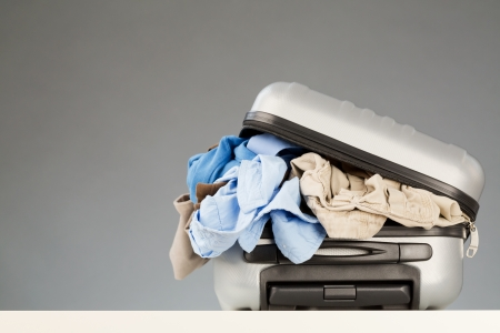 packing: A suitcase over-packed with various casual clothes lying on a white surface with a gray background. Stock Photo
