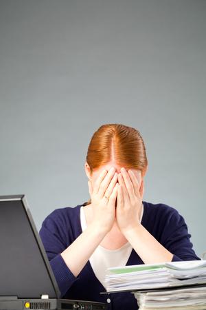 A fogalmi kép a stresszes munka - egy fiatal nő arcát temette a kezébe mögé egy íróasztal a papírmunkát és a számítógép. Stock fotó