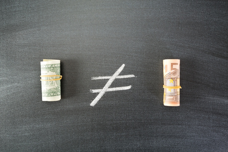 compared: Image of US dollar bills compared to Euro bills over a blackboard, top view.