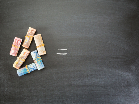 equals: Rolls of Euro banknotes photographed next to an equals sign over a blackboard with copy space.
