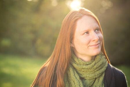 Portré egy fiatal nő egy parkban álmodozás és keresi távol a kamera. Stock fotó