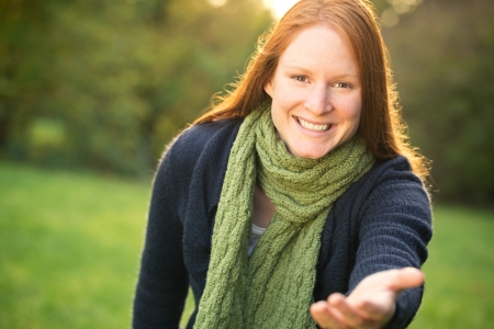 A smiling young woman in a park stretching her hand to the camera - inviting or asking someone to come or offering help.