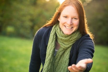 Een lachende jonge vrouw in een park stretching haar hand naar de camera - uitnodigen of iemand te vragen om te komen of het aanbieden van hulp.