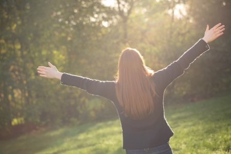 A young woman with open arms in a park during an autumn sunset enjoying the sunlight.