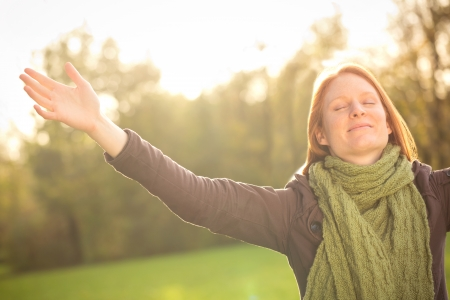 Happy young woman with open arms in a park meditating, worshipping or simply enjoying the Autumn season. Stock Photo