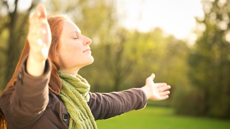 Woman worshiping with open arms or taking in the Autumn sun in a park. Stock Photo