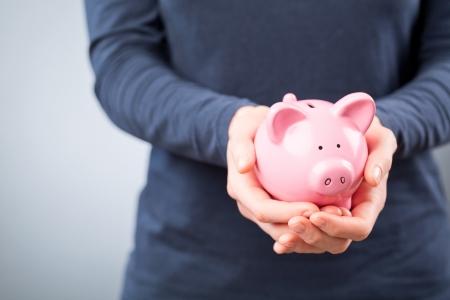 Egy fiatal nő, kezében egy rózsaszín kerámia malacka bank kezében.