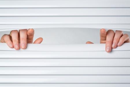 Two female hands opening a peeking hole in closed venetian blinds.