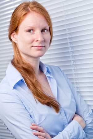 A young business woman with red hair standing next to an office window with closed blinds or shutters. photo