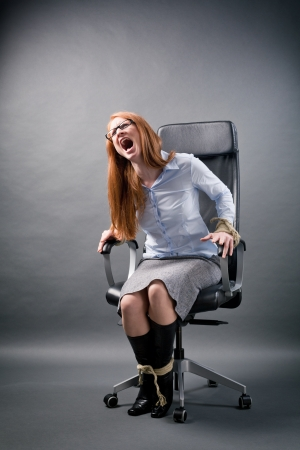 A young secretary or business assistant tied up to an office chair screaming for help. photo