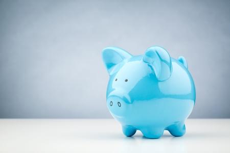 배경에 복사 공간 흰색 책상 표면에 서있는 푸른 돼지 저금통의 가로 이미지.