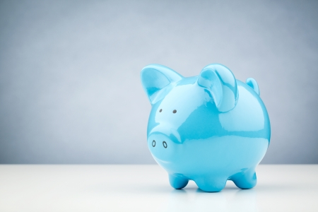 Horizontal image of a blue piggy bank standing on a white desk surface with copy space on the background.