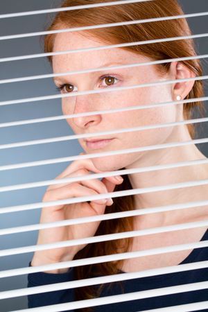 A confident young businesswoman in thought while looking through open window blinds at an office. photo