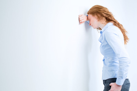 A stressed, exhausted or failed businesswoman leaning with her head against a white wall. photo