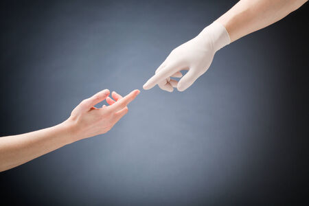A hand of a doctor or a medical person in a white latex glove touching a bare female hand. Stock Photo - 25108976