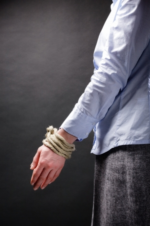 Tied up hands of a young businesswoman pointing down with copy space above them. photo